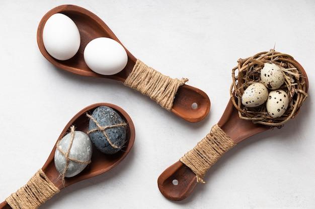 Mise à plat d'oeufs de pâques dans des cuillères en bois