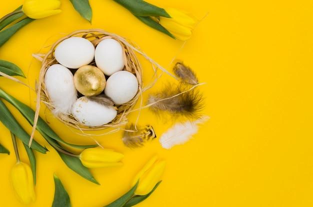 Mise à plat d'oeufs de pâques dans un panier avec des tulipes et des plumes