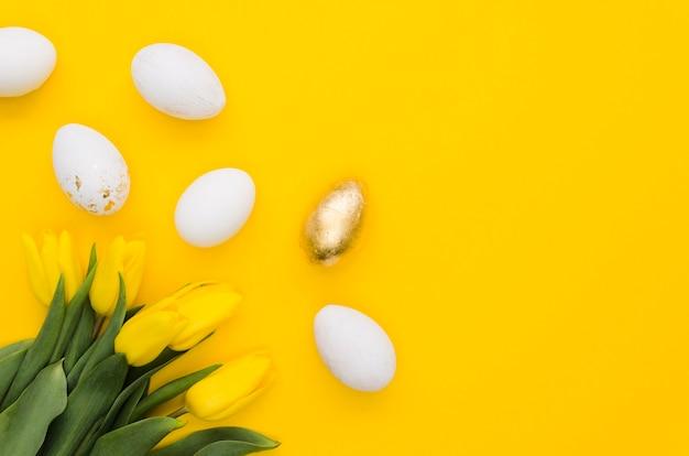 Mise à plat d'oeufs de pâques avec tulipes et espace copie