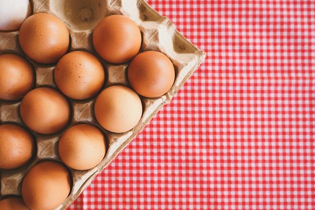 Mise à plat d'œufs de poule dans une boîte en carton sur une nappe rose classique