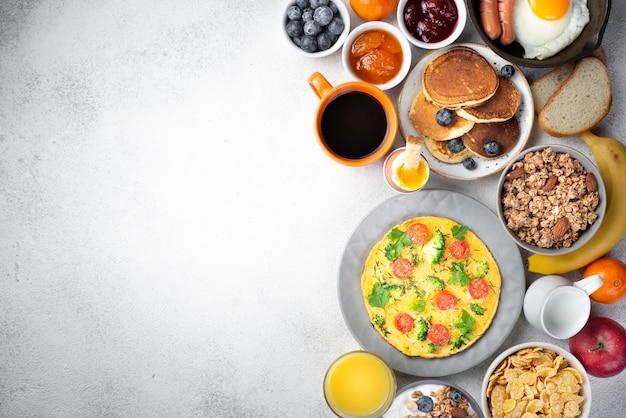 Mise à plat d'omelette et de crêpes pour le petit déjeuner avec des céréales et de la confiture