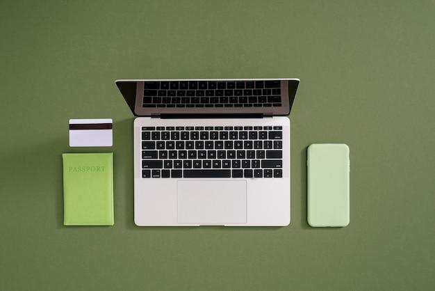 Mise à plat d'un ordinateur portable, d'une carte de crédit, d'un téléphone portable et d'un passeport sur vert
