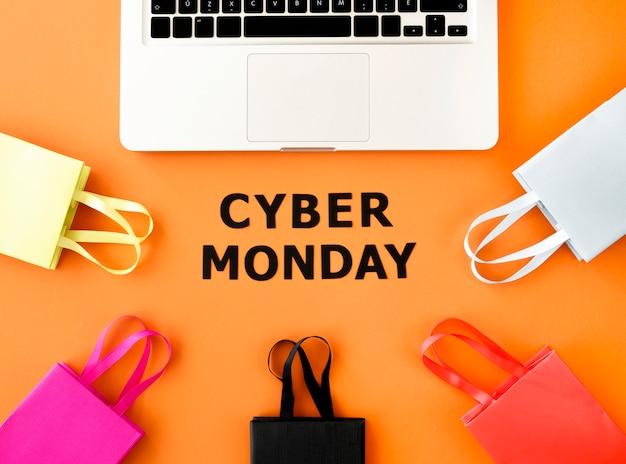 Mise à plat de l'ordinateur portable avec des sacs à provisions pour cyber lundi