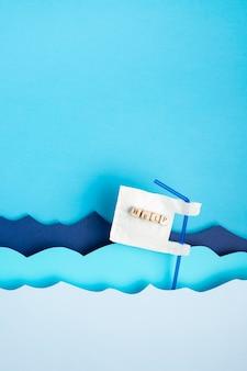 Mise à plat de paille en plastique avec de l'aide dans les vagues de l'océan en papier