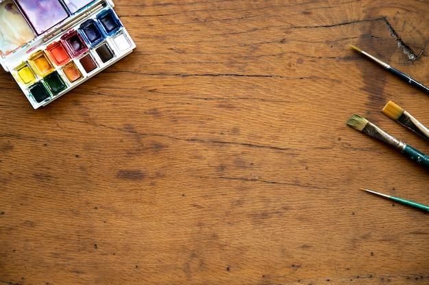 Mise à plat de la palette d'aquarelle et des pinceaux sur une table en bois. notion de créativité. espace de copie.
