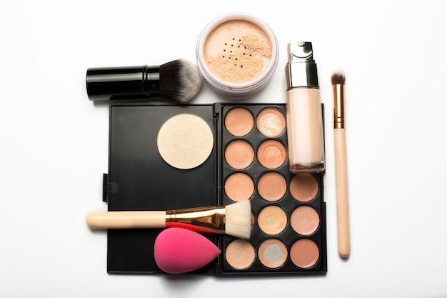 Mise à plat de la palette de contour, pinceaux de maquillage et poudre minérale