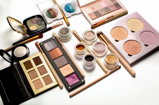 Mise à plat de palettes d'ombres à paupières professionnelles, de surligneurs et de pinceaux de maquillage sur fond blanc