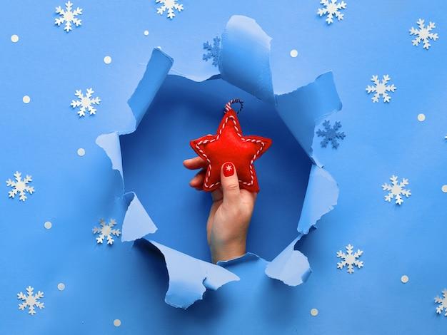 Mise à plat de papier bleu avec des flocons de neige et trou déchiré au milieu