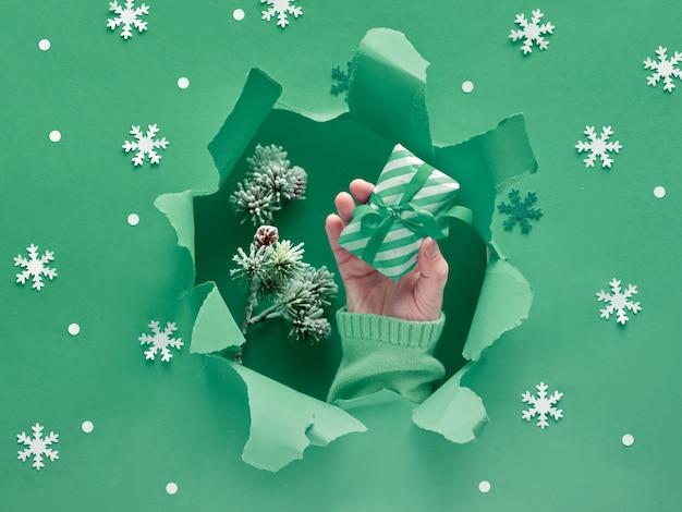 Mise à plat de papier vert avec des flocons de neige et un trou déchiré au milieu