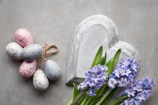 Mise à plat de pâques avec des fleurs de jacinthe bleues, des oeufs de pâques et un grand coeur sur le mur clair