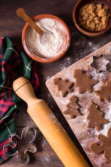 Mise à plat de pâte à biscuits de noël avec des formes d'arbre de noël