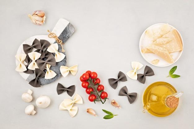 Mise à plat avec des pâtes farfalle italiennes traditionnelles et des ingrédients de cuisine. concept de cuisine italienne traditionnelle. vue de dessus