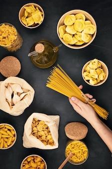 Mise à plat avec des pâtes italiennes biologiques traditionnelles et des ingrédients de cuisine dans des sacs en coton réutilisables et des récipients en verre. zéro déchet, concept sans plastique