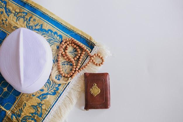 Mise à plat de perles de prière et casquette sur le tapis de prière avec le livre saint al coran il y a une lettre arabe qui signifie le livre saint