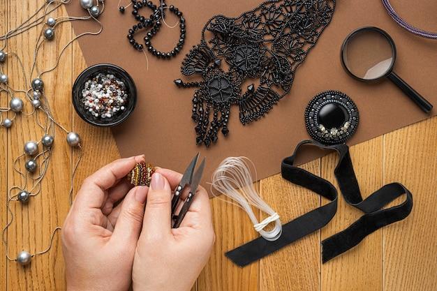 Mise à plat de la personne faisant des travaux de perles avec des ciseaux