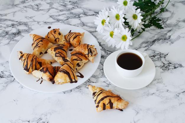 Mise à plat de petits pains au chocolat frais, fleurs et tasse de café sur fond de marbre