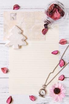 Mise à plat photographie de stock pétales de fleurs violettes lettre enveloppe papier verre transparent bouteille horloge de poche arbre de noël artisanat