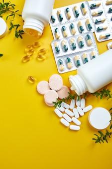 Mise à plat de pilules, huile de poisson, vitamines sur surface jaune