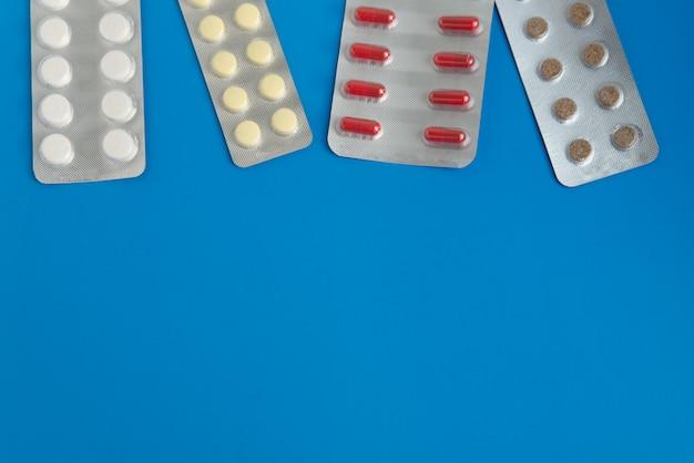 Mise à plat des plaquettes alvéolées avec copyspace sur le fond bleu. disposition des pilules