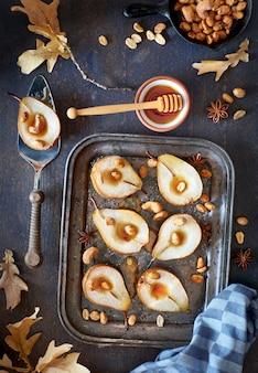 Mise à plat avec un plateau de poires au four avec des noix caramélisées sur bois foncé avec des feuilles d'automne