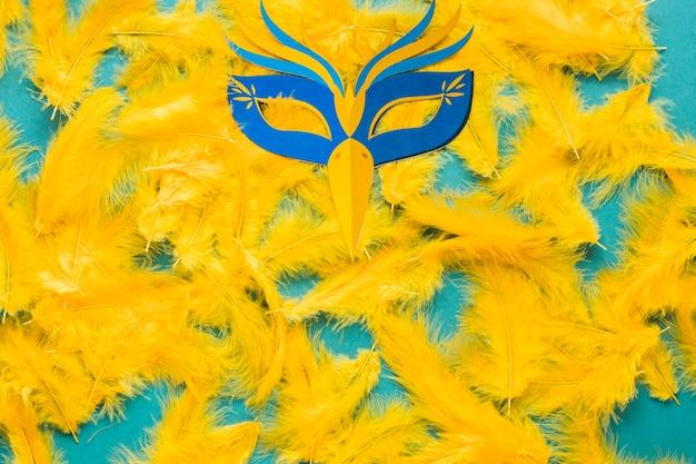 Mise à plat de plumes jaunes et masque de carnaval