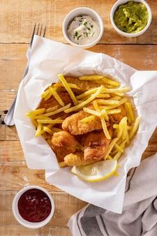 Mise à plat de poisson et frites avec des sauces