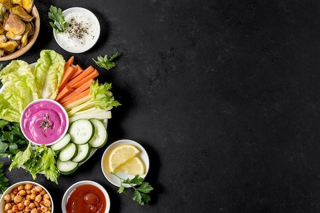 Mise à plat de pommes de terre rôties dans un bol avec des légumes et de l'espace de copie