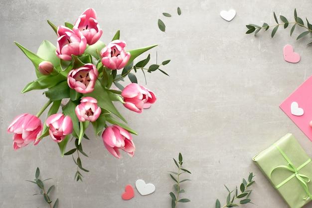 Mise à plat de printemps avec bouquet de tulipes roses, feuilles d'eucalyptus et coffrets cadeaux sur la surface de la pierre