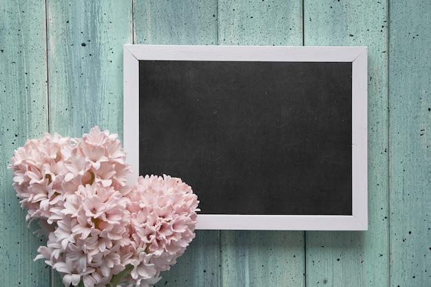Mise à plat de printemps avec des fleurs de jacinthe rose et tableau noir avec texte