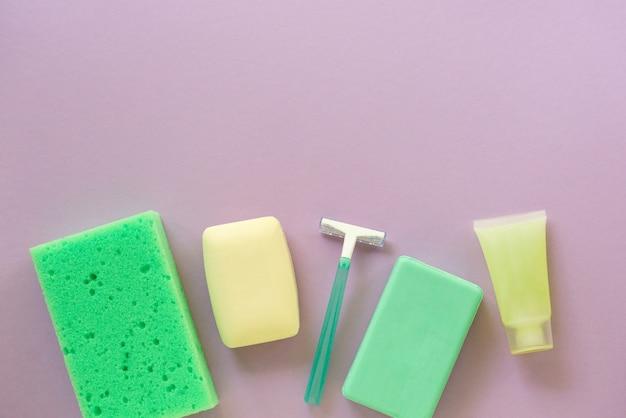 Mise à plat des produits de bain et d'hygiène. rasoir, pain de savon et gant de toilette sur fond lilas. espace pour le texte.
