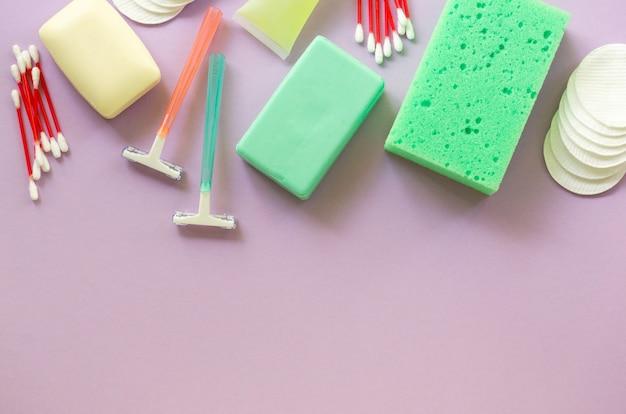 Mise à plat des produits de bain et d'hygiène. rasoirs, pains de savon et gant de toilette sur fond lilas. espace pour le texte