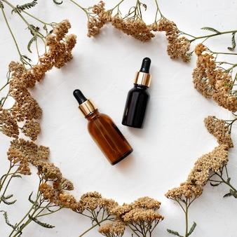 Mise à plat des produits d'huiles essentielles de soins de la peau de bouteille en verre compte-gouttes pour maquette dans un style minimal avec sur fond blanc.