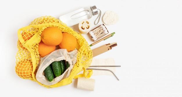 Mise à plat de produits respectueux de l'environnement, sac écologique en coton naturel avec fruits et légumes sur un mur blanc, respectueux de l'environnement et sans déchets. bâtons d'oreille en bois, gant de toilette en luffa