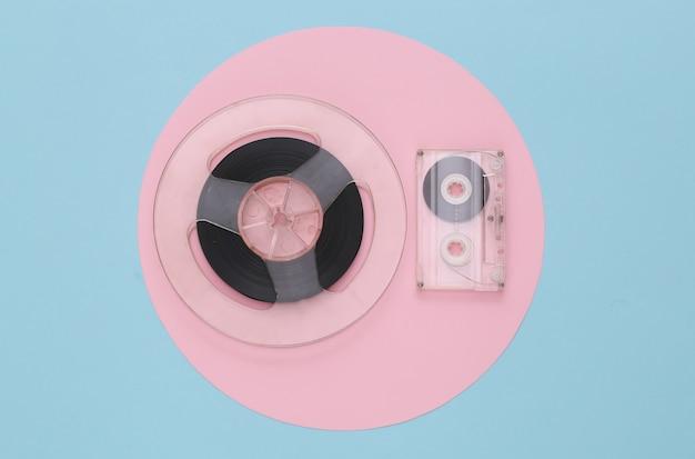 Mise à plat rétro. bobine de bande magnétique audio et cassette audio sur pastel bleu rose