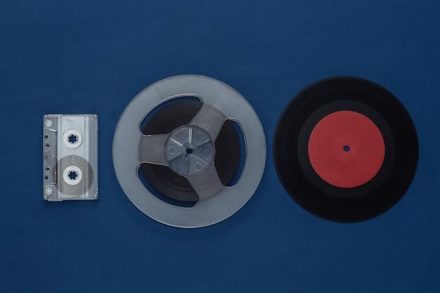 Mise à plat rétro. bobine de bande magnétique audio, cassette audio et vidéo sur bleu classique