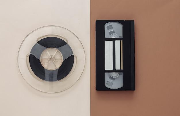 Mise à plat rétro. bobine de bande magnétique audio et cassette vidéo sur beige marron
