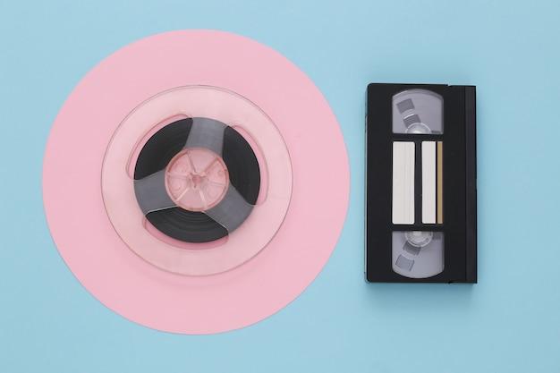 Mise à plat rétro. bobine de bande magnétique audio et cassette vidéo sur pastel bleu rose