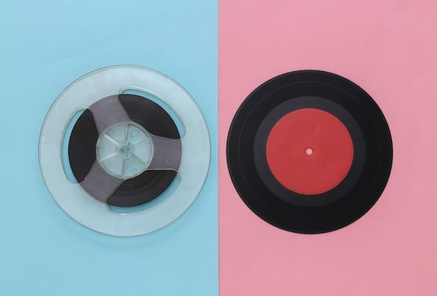Mise à plat rétro. bobine de bande magnétique audio et plaque de vinyle sur pastel bleu rose
