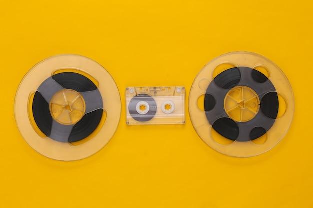 Mise à plat rétro. deux bobines de bande magnétique audio et cassette audio sur jaune