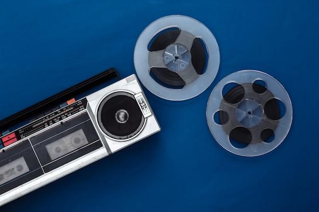 Mise à plat rétro. enregistreur de cassettes stéréo portable rétro et bobine de bande magnétique audio sur bleu classique