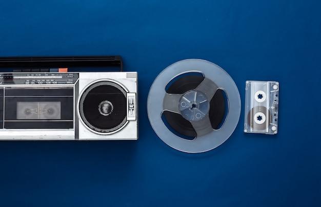 Mise à plat rétro. enregistreur de cassettes stéréo portable rétro et bobine de bande magnétique audio, cassette audio sur bleu classique
