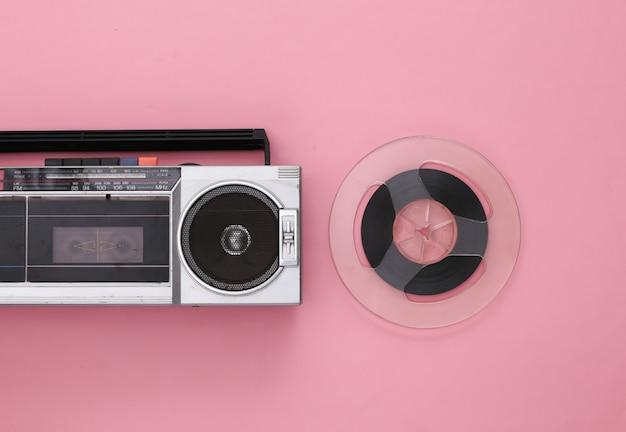 Mise à plat rétro. enregistreur de cassettes stéréo portable rétro et bobine de bande magnétique audio sur rose
