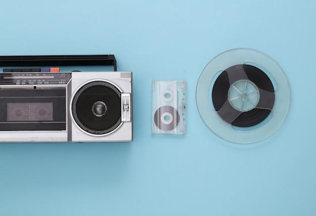 Mise à plat rétro. enregistreur stéréo portable rétro, cassette et bobine de bande magnétique audio sur pastel bleu