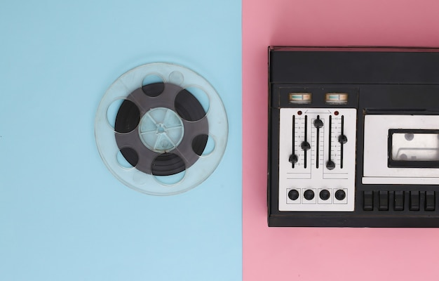 Mise à plat rétro. enregistreur stéréo rétro et bobine de bande magnétique audio sur pastel bleu