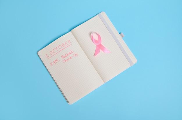 Mise à plat d'un ruban rose, sur un bloc-notes ouvert avec des inscriptions rappelant un examen médical. 1er octobre, journée mondiale du cancer du sein, soins de santé des femmes et concept médical, isolé avec espace de copie