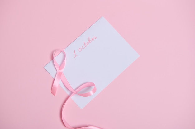 Mise à plat d'un ruban rose avec une extrémité sans fin allongée sur une feuille de papier blanc avec le lttering 1er octobre, symbole international du mois de la sensibilisation au cancer du sein. soins de santé de la femme et concept médical