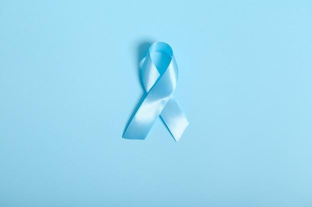 Mise à plat d'un ruban de satin bleu, couleur d'arc symbolique sensibilisant à la journée du diabète sur fond bleu avec espace de copie pour l'annonce, 14 novembre. concept de sensibilisation à la journée mondiale du diabète.