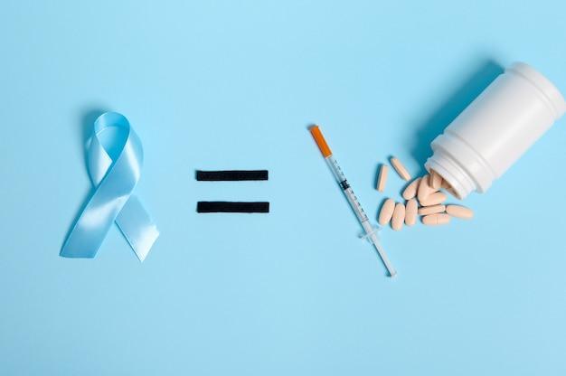 Mise à plat d'une seringue à insuline et de pilules pharmaceutiques dispersées dans un conteneur sur fond bleu, signe égal et ruban bleu, symbole de la journée mondiale de sensibilisation au diabète. espace de copie pour la publicité médicale
