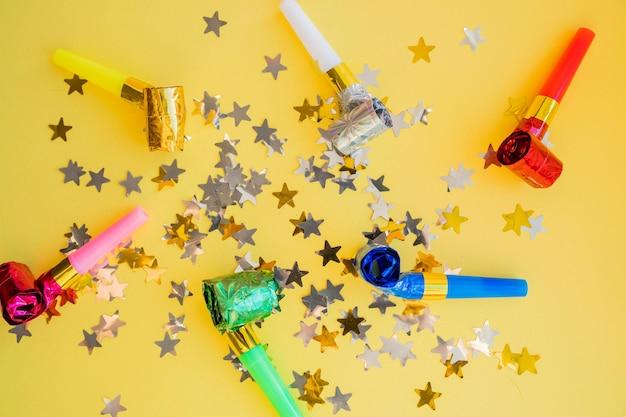 Mise à plat de sifflets et de confettis étoiles attributs de célébration d'anniversaire. cornes de fête, confettis brillants