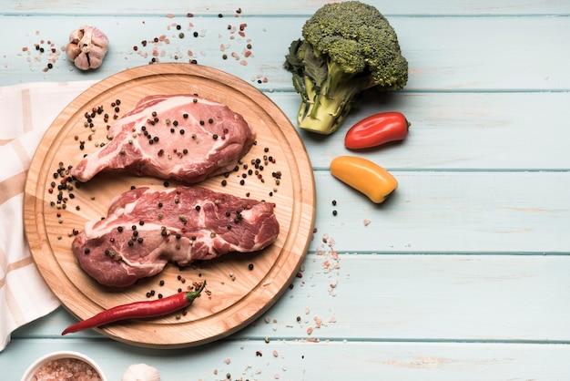 Mise à plat de steaks crus sur planche de bois avec des ingrédients
